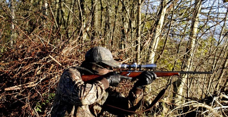 Man hunting in woods with bolt action